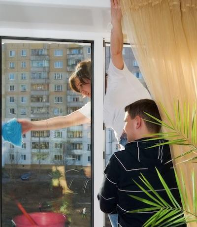 Putzfrau hängt während der Glasreinigung in Nürnberg aus dem Fenster https://gebaeudereiniger-nuernberg.de reinigung